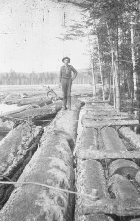 Man standing on floating logs